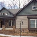 stone & siding home with green top
