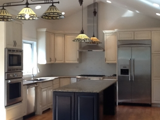 Kitchen interior designed with custom light fixtures hanging from high ceiling