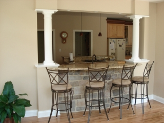 Kitchen behind counter with pillars dividing dining room from kitchen