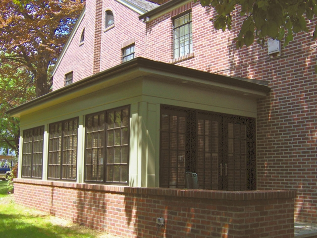 Sunroom installed along the side of house with matching brick wall